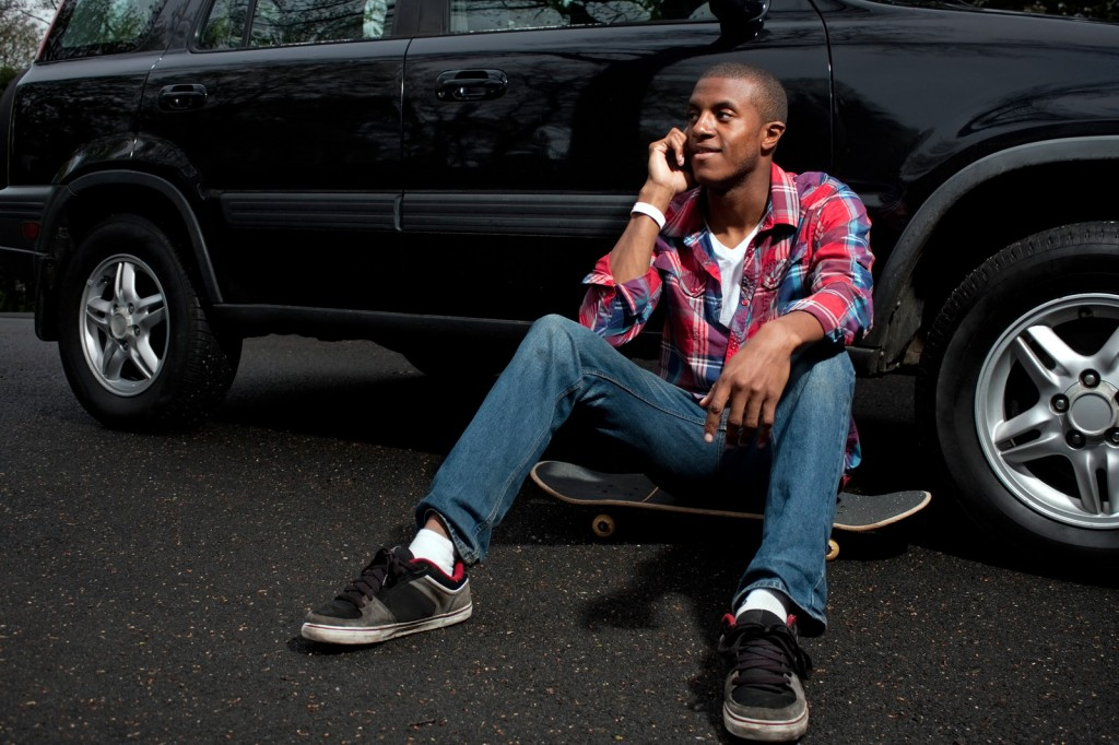 Young man sitting on skate board leaning against SUV talking on smartphone