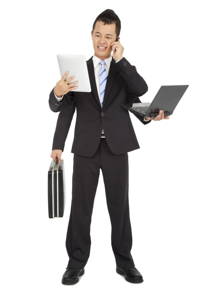 Business man holding multiple devices.