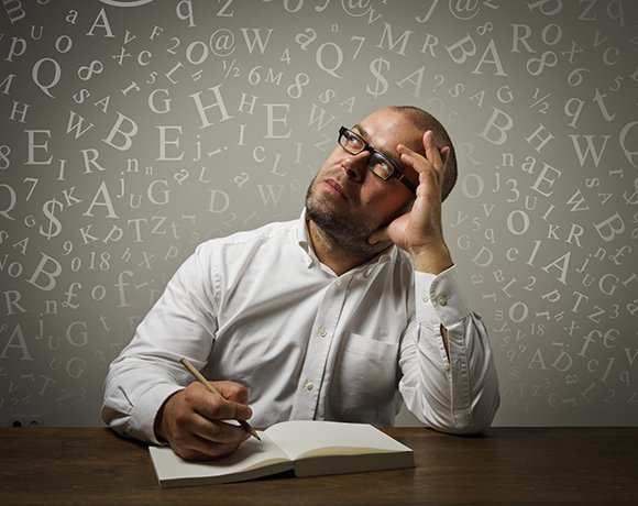 Businessman thinking with letters and numbers swirling around