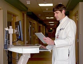 Hospitalist Geoffrey Marx, M.D., reviews an EHR on a tablet computer at Athens (Ga.) Regional Health System