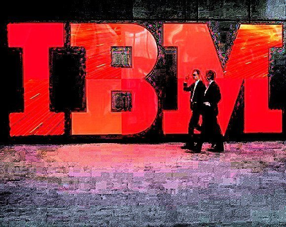 Two IBM employees walk past the IBM logo