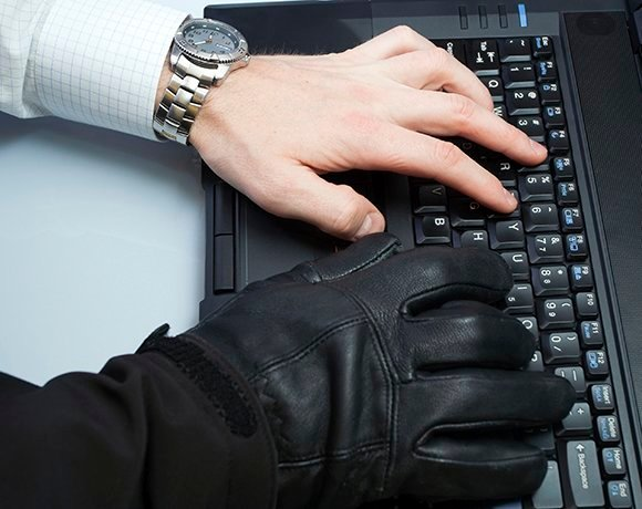 Two hands on keyboard, one in a black leather glove
