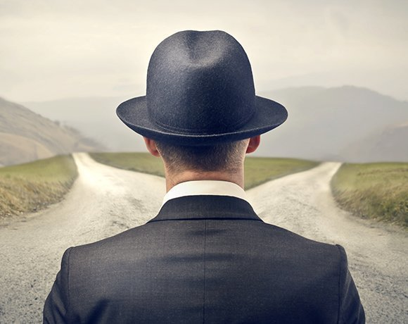 Man wearing hat looking down a divided road