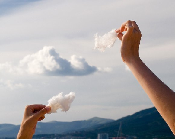 two hands placing cotton clouds in sky