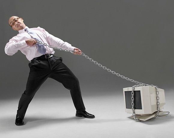 businessman dragging a computer wrapped up in chains