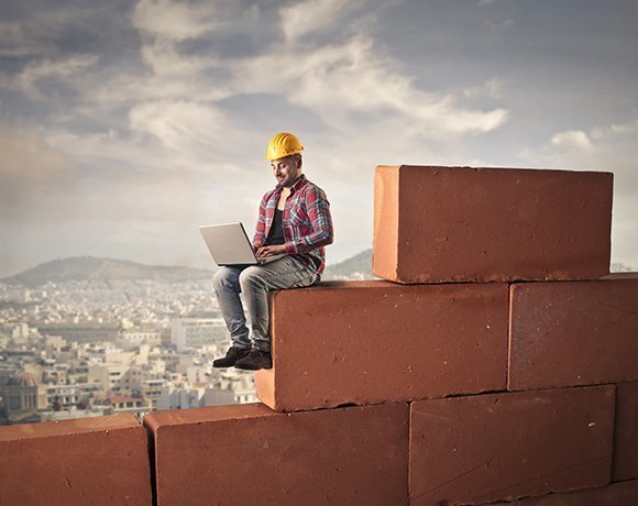 construction worker on wall with laptop