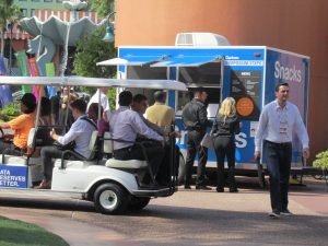 Attendees of the recent Gartner Symposium/ITxpo ride in a golf cart near the Dolphin and Swan hotels.