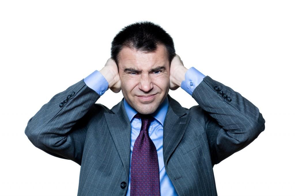 Man holding his ears pretending not to listen.