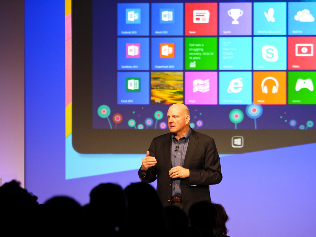 Microsoft CEO Steve Ballmer standing in front of a giant projection of Windows 8.