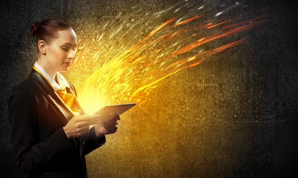 Business woman holding an iPad while sparks fly out of it.