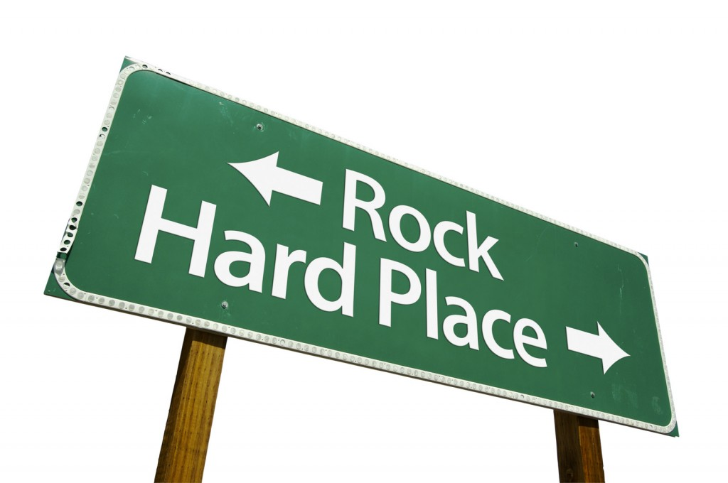 Street sign pointing to rock in one direction and hard place in another.