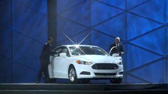 A droite, Robert Leblanc, vice président du middleware chez IBM. A gauche, Vijay Sakaran, directeur du développement d'applications chez Ford, aux côté de le Ford Fusion
