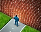 Man standing in front of brick wall obstacle