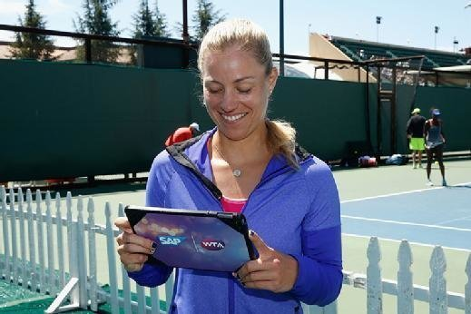 Tennis pro Angelique Kerber looks at a tablet running the SAP Tennis Analytics application.