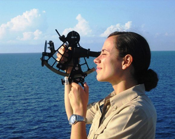 a woman navigates the ocean using a sextant